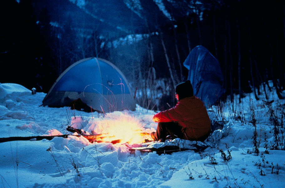 winter camping at night man sitting by fire near tent