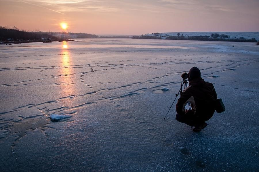 a man with a camera during sunrise on the ice