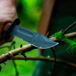 man holding hunting knife near twig
