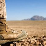 soldier foot with military boot in desert with mountain in distance