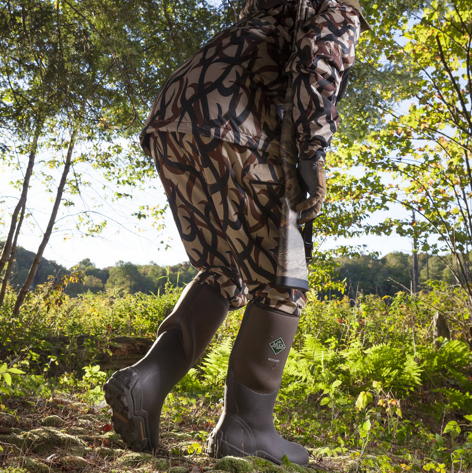 hunter wearing rubber boots lying low in the forest