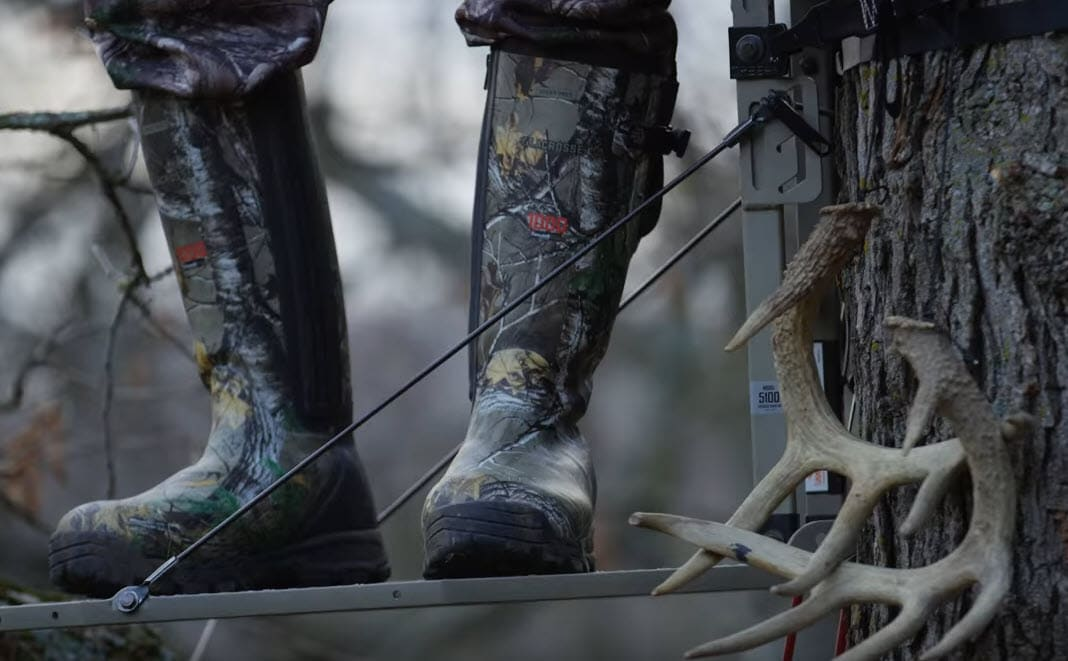 warm rubber hunting boots on feet standing on tree stand