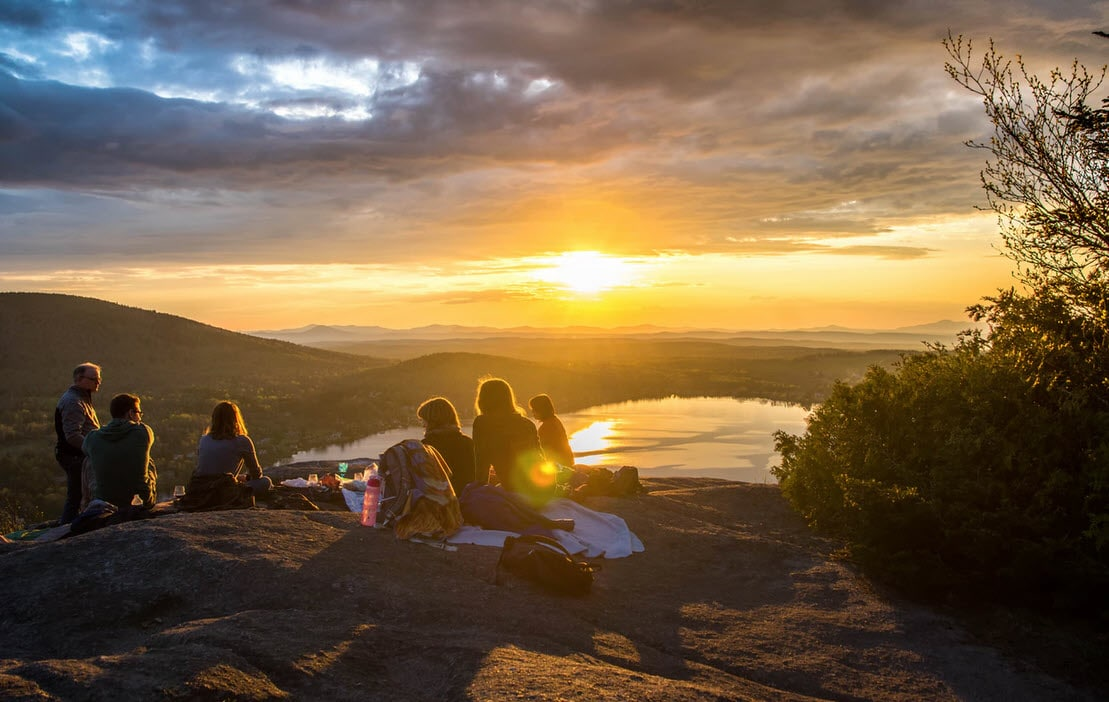 group of hikers on mountain at sunset